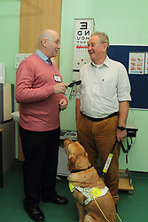 Volunteer holding pinhole glasses with patient in consulting room in eye clinic at QMC hospital, Nottingham.