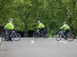 © Licensed to London News Pictures. 14/05/2020. London, UK. Police have a cycling training session in Hyde Park in London as bike cops continue to patrol the parks after the Government relaxes the law on lockdown to let people spend more time outside to have picnics, sunbath and meet up with other people as weather experts predict a warmer week ahead. Photo credit: Alex Lentati/LNP