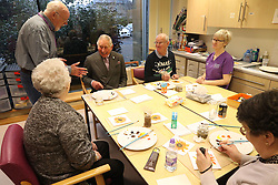 Prince Charles (known as The Duke of Rothesay when in Scotland, centre left) taking part in a painting class during his visit to the Ayrshire Hospice in Ayr where he met patients and their families, staff and volunteers, with standing-volunteer occupational therapist George Bell (left) and patient Jim Fitzsimmons (centre right) and occupational therapist Joan Carrigan (right).