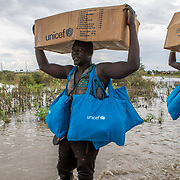 NGO workers wade through flood water to transport dignity kits and food to distribution points for displaced communities, in Pibor, Boma State, South Sudan on 6 November 2019 // Photo credit: UNICEF South Sudan/de la Guardia