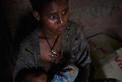 Fifteen-year-old Destaye breastfeeds her son near Bahir Dar, Ethiopia on Aug. 12, 2012. Destaye and her husband Addisu, 27, divide their time between working in the fields and taking care of their 6-month-old baby. Like many other young couples, they tend to the domestic, economic and personal demands of being young parents. At the time of their marriage, when Destaye was age 11, she was still in school and her husband expressed interest in letting her continue her education. Since the birth of their son, however, she has had to confine her life exclusively to being a wife and mother.