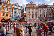 A crowd in-between bursting bubbles created by a street  perfomer in-front of the Old Town hall at Old Town Square in Prague.