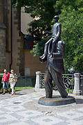 The Kafka sculpture by Jaroslav Rona, with two people a man and a woman walking past it, Prague, Czech Republic. .