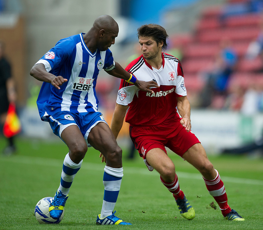 Middlesbrough's George Friend and Wigan Athletic's Emmerson Boyce<br /> <br /> Photo by Stephen White/CameraSport<br /> <br /> Football - The Football League Sky Bet Championship - Wigan Athletic v Middlesbrough - Sunday 25th August 2013 - DW Stadium - Wigan<br /> <br /> © CameraSport - 43 Linden Ave. Countesthorpe. Leicester. England. LE8 5PG - Tel: +44 (0) 116 277 4147 - admin@camerasport.com - www.camerasport.com