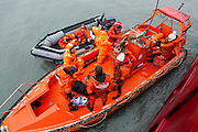 Russian, Polish, and Norwegian oceanographers arrive by inflatable boat to the MS Stalbas during a science diplomacy mission around Svalbard.