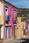 The brightly painted pink Hotel Centenario Centro in the beautiful colonial village of Bernal, Queretaro, Mexico. Bernal is a quaint colonial town known for the Pena de Bernal, a giant monolith which dominates the tiny village is the third highest on the planet.