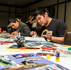 IRVINE, CA - MARCH 2: Student John Velasco(R) creates collages from magazines clips at the Treasure Room during the Working Wardrobes Dream Girls & Distinguished Gentlemen 2013 event at the Irvine Hilton in Irvine, CA. Working Wardrobes (http://www.workingwardrobes.org) is a non-profit organization located in Costa Mesa, CA. PHOTO: © 2013 SILVEX.PHOTOSHELTER.COM.