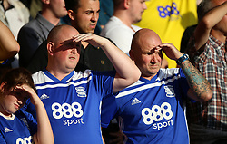 Birmingham City fans in the stands shield their eyes from the sun