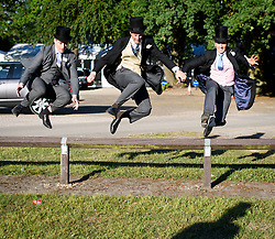 © Licensed to London News Pictures. 21/06/2018. London, UK. Racegoers jump over  fence at Ladies Day at Royal Ascot at Ascot racecourse in Berkshire, on June 21, 2018. The 5 day showcase event, which is one of the highlights of the racing calendar, has been held at the famous Berkshire course since 1711 and tradition is a hallmark of the meeting. Top hats and tails remain compulsory in parts of the course. Photo credit: Ben Cawthra/LNP