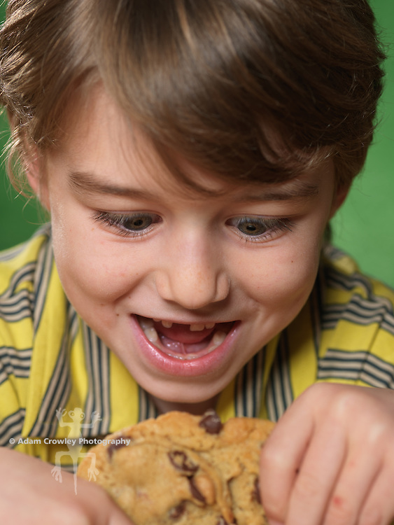 Portrait of boy (7 years old) eating cookie with missing front tooth.