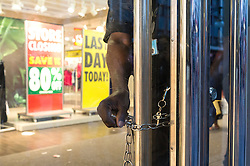 © Licensed to London News Pictures. 13/08/2016. Security guard padlocks the front doors as British Homes Stores Oxford Street Flagship store closes on its last day of trading. London, UK. Photo credit: Ray Tang/LNP