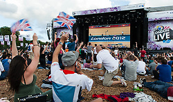 © Licensed to London News Pictures. 03/08/2012. London, UK. Fans in Hyde Park watch as the Team GB Cycling Team beat their own world record and defend the men's Olympic  pursuit title to win Friday's second Gold medal for Great Britain.  Photo credit : Richard Isaac/LNP