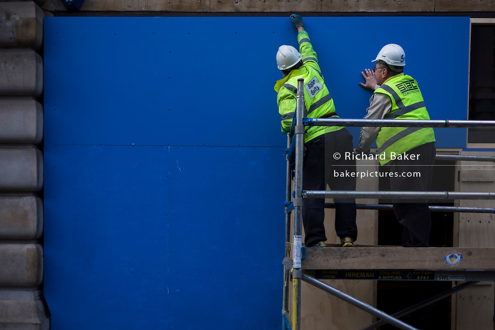 Construction workers and large blue panel in London street.