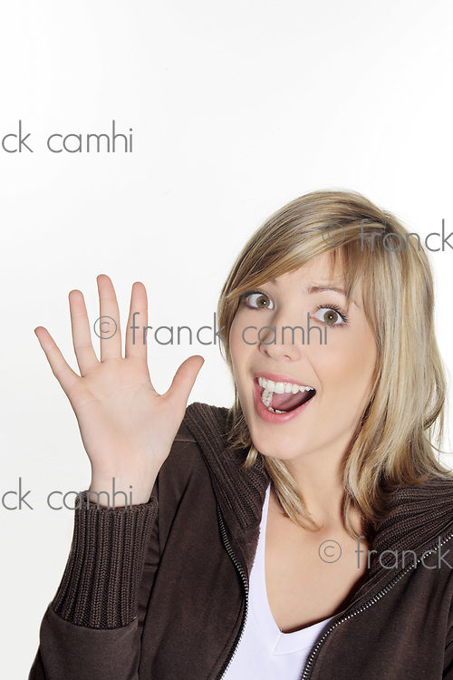 portrait in studio on a white background of a young blond caucasian expressive and smiling woman making sign with her hands