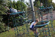 Three brothers explore a playpark climbing structure, on 25th August, in Ruskin Park, London borough of Lambeth, England.