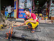 """10 AUGUST 2014 - BANGKOK, THAILAND: A man lights candles for Ghost Month in front of his shop in the Chinatown section of Bangkok. The seventh month of the Chinese Lunar calendar is called """"Ghost Month"""" during which ghosts and spirits, including those of the deceased ancestors, come out from the lower realm. It is common for Chinese people to make merit during the month by burning """"hell money"""" and presenting food to the ghosts.    PHOTO BY JACK KURTZ"""