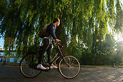 Een man fietst staand op de pedalen door Utrecht.<br /> <br /> A man cycles standing in Utrecht.