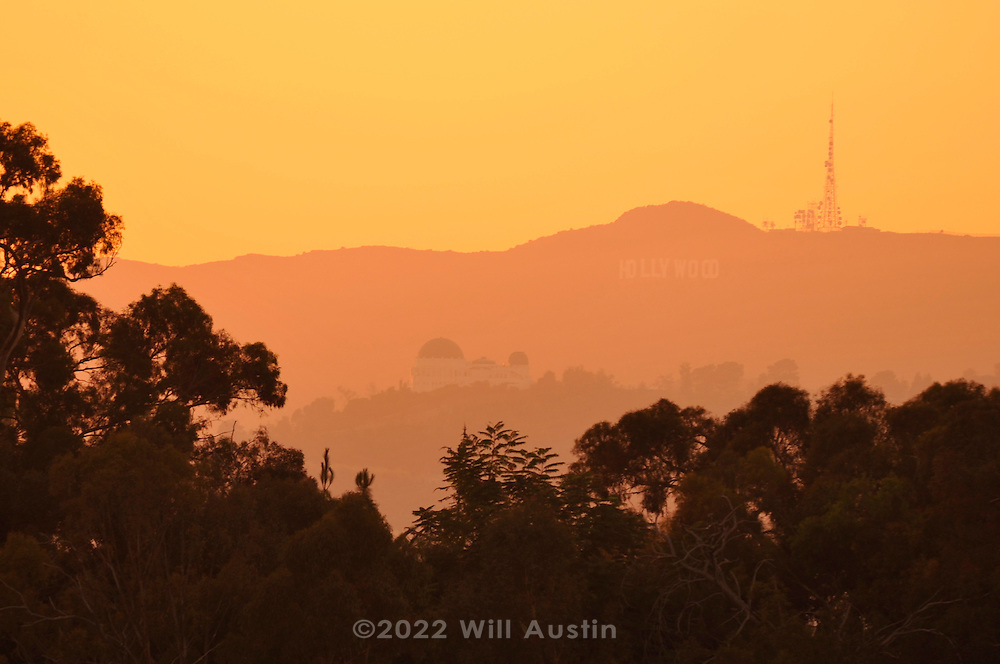 View of the Hollywood sign and the Griffith Observatory in Los Angeles at sunset.