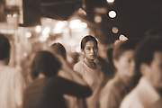 A woman stands out in a crowd full of people in a town in Thailand.
