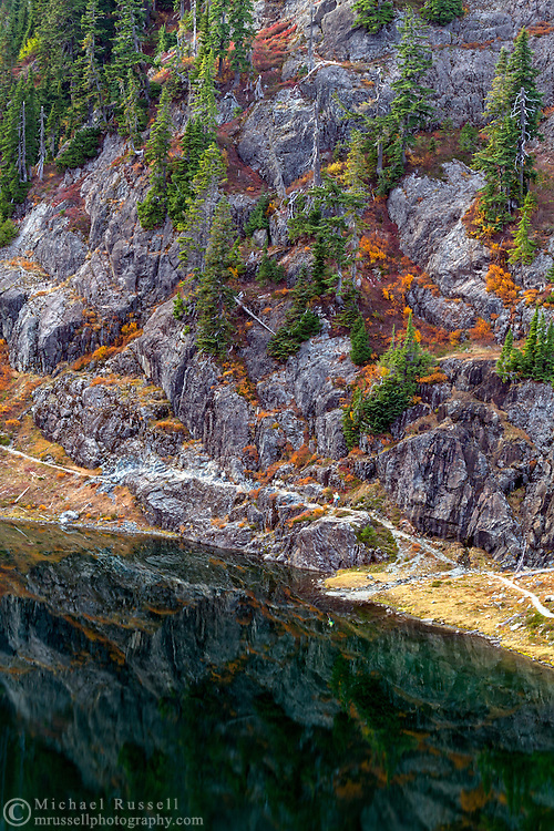 Fall foliage and the Chain Lakes Trail below Mount Herman reflect in the water of Bagley Lakes.   Photographed in the fall from the Heather Meadows Recreation area of the Mount Baker-Snoqualmie National Forest, Washington State, USA.