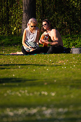 A man play guitar as a woman enjoys his company as crowds enjoy the unseasonably warm and sunny weather in Regents Park, London. London, February 26 2019.