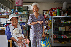 Two old friends visit inside a store in Ogimi, also know as the Longevity Village in Okinawa, Japan.