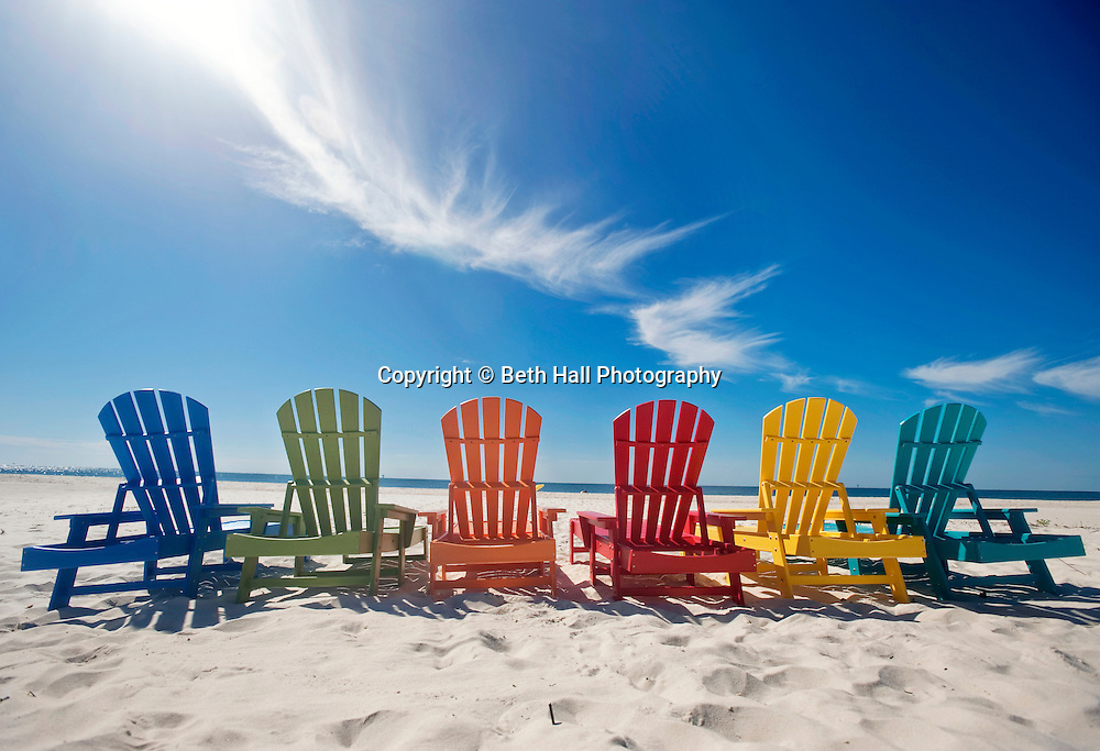 A row of colorful Adirondack lounge chairs lined up on the beach under a blue sky.