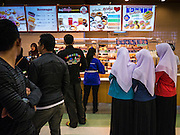 08 JULY 2013 - PATTANI, PATTANI, THAILAND:  Muslim school girls look at the menu of a fast food restaurant in Pattani Monday afternoon, the day before Ramadan. Ramadan starts July 9 and Monday was the last day observant Muslims were able to eat and drink during daylight hours. Muslims fast during the holy month of Ramadan, taking breakfast before dawn and not eating again until after sunset. The restaurants in Pattani, a Muslim majority city in southern Thailand, were packed Monday afternoon and evening.    PHOTO BY JACK KURTZ