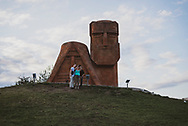 """Tourists take a selfie in front of the """"We Are Our Mountains"""" monument, located on the outskirts of Stepanakert, Nagorno-Karabakh. The sculpture, hewn from volcanic tufa and completed in 1967 by Sargis Baghdasaryan, depicts an old man and woman who represent the mountain people of Karabakh.<br /> <br /> (September 22, 2016)"""