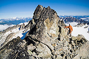 Brian Polagye enjoys the views standing against the summit block of Austera Peak, North Cascades National Park, Washington.