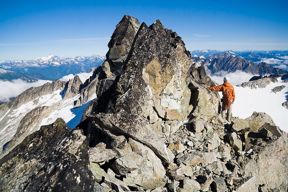 Brian Polagye enjoys the views standing against the summit block of Austera Peak, North Cascades National Park, Washington.