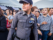 19 OCTOBER 2014 - BANG BUA THONG, NONTHABURI, THAILAND:  A Thai police officer walks through the crowd at Apiwan Wiriyachai's cremation at Wat Bang Phai in Bang Bua Thong, a Bangkok suburb, Sunday. Apiwan was a prominent Red Shirt leader. He was member of the Pheu Thai Party of former Prime Minister Yingluck Shinawatra, and a member of the Thai parliament and served as Yingluck's Deputy Prime Minister. The military government that deposed the elected government in May, 2014, charged Apiwan with Lese Majeste for allegedly insulting the Thai Monarchy. Rather than face the charges, Apiwan fled Thailand to the Philippines. He died of a lung infection in the Philippines on Oct. 6. The military government gave his family permission to bring him back to Thailand for the funeral. His cremation was the largest Red Shirt gathering since the coup.    PHOTO BY JACK KURTZ