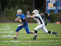 Kearsarge running back Jacob Jones attempts to outrun the tackle by Monadnock's Jake Poulin during NHIAA Division V semi final football Saturday night.  (Karen Bobotas/for the Concord Monitor)