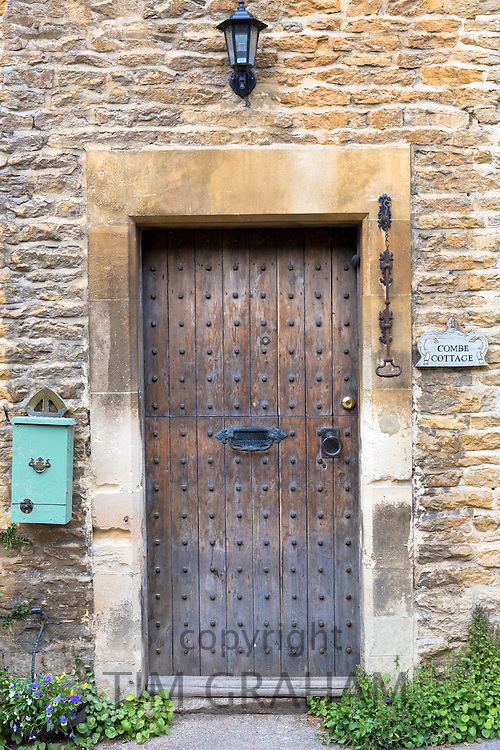 Traditional English studded oak timber door of country cottage in quaint village of Castle Combe in Wiltshire, The Cotswolds, UK