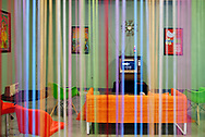 Garden City, New York, U.S. July 25, 2019. American 1960s style living room, seen through colorful hanging strips room divider, has CBS Apollo 11 news coverage on a tube TV set, with simulation of July 20, 1969, lunar module Moon Landing. The Cradle of Aviation Museum set was for visitors to take photos in during its recent Apollo 11 Countdown on the 50th Anniversary of man first walking on the moon.