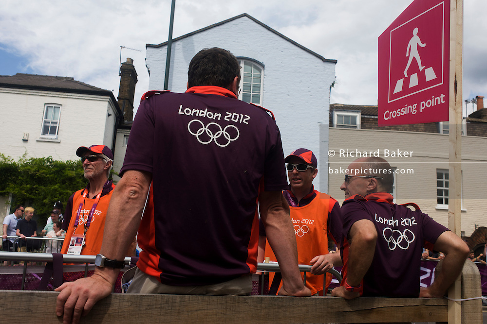 Olympic volunteers await the arrival of road cycling competitors on the first day of competition of the London 2012 Olympic 250km mens' road race. London 2012 volunteers are called 'Games Makers', as they are helping to make the Games happen. Up to 70,000 Games Makers take on a wide variety of roles across the venues: from welcoming visitors; to transporting athletes; to helping out behind the scenes in the Technology team to make sure the results get displayed as quickly and accurately as possible. Games Makers come from a diverse range of communities and backgrounds, from across the UK and abroad. The vast majority are giving up at least 10 days to volunteer during the Games..