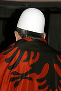 """Kosovo, Pristina<br /> Saturday, February 16, 2008<br /> <br /> An old Albanian man, cover his body with Albanian National flag, also he cover his head with Albanian national White Heat, which in Albanian means """"Plis""""<br /> This old man, use to walk around Grand HOTEL iin Pristina"""