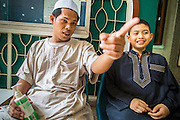 "11 JANUARY 2013 - BANGKOK, THAILAND:    A teacher talks to a student at a Muslim school in the Ban Krua neighborhood in Bangkok. The Ban Krua neighborhood of Bangkok is the oldest Muslim community in Bangkok. Ban Krua was originally settled by Cham Muslims from Cambodia and Vietnam who fought on the side of the Thai King Rama I. They were given a royal grant of land east of what was then the Thai capitol at the end of the 18th century in return for their military service. The Cham Muslims were originally weavers and what is known as ""Thai Silk"" was developed by the people in Ban Krua. Several families in the neighborhood still weave in their homes.        PHOTO BY JACK KURTZ"