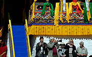 European Tourists armed with cameras lined up under the brightly decorated VIP grandstand at the Paro festival. Paro, Bhutan. Druk Yul. 11 November 2007