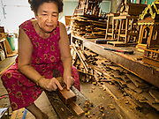 02 NOVEMBER 2016 - BANGKOK, THAILAND:  HONG, 77 years old, the matriarch of the last family making spirit houses in the Ban Fuen community, planes teak wood for use in a spirit house. There used to be 10 families making traditional spirit houses out of teak wood in Ban Fuen, a community near Wat Suttharam in the Khlong San district of Bangkok. The area has been gentrified and many of the spirit house makers have moved out, their traditional wooden Thai houses replaced by modern apartments. Now there is just one family making the elaborate spirit houses. The spirit houses are made by hand. It takes three days to make a small one and up to three weeks to make a large one. Prices start at about $90 (US) for a small one. The largest, most elaborate ones can cost over $1,000 (US). Almost every home and most commercial buildings in Thailand have a spirit house, which is a shrine to the protective spirit of a the land. Spirit houses are also common in Burma, Cambodia, and Laos.       PHOTO BY JACK KURTZ