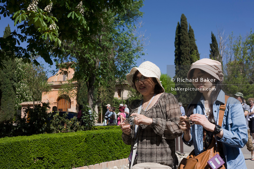 Two women tourists from Asia walk in the sunshine at Alhambra, both holding cameras.