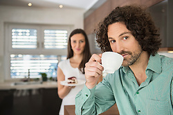 Man drinking cup of coffee and his wife with a cake in background, Munich, Bavaria, Germany