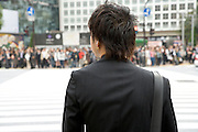 young business person waiting to cross the Hachiko square zebra crossing at Shibuya station in Tokyo Japan