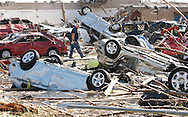 A man walks through the tornado destroyed cars of teachers at Briarwood elementary school in Oklahoma City, Oklahoma May 22, 2013.  Rescue workers with sniffer dogs picked through the ruins on Wednesday to ensure no survivors remained buried after a deadly tornado left thousands homeless and trying to salvage what was left of their belongings. Curvature of horizon in the photo is due to an ultra-wide angle lens.  REUTERS/Rick Wilking (UNITED STATES)