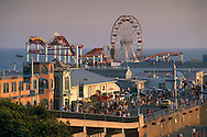 Sunset light on rollercoaster and ferris wheel and crowds of people on the Santa Monica Pier, Los Angeles County, California