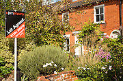 Let Agreed sign outside garden of pretty cottage, Woodbridge, Suffolk, England