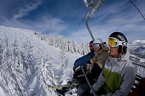 Three young men riding chairlift at Kirkwood ski resort near Lake Tahoe, CA.