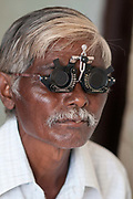 India. Orissa. Village eye camp at Fatak, Sundergarh. September 2012. An ophthalmic assistant tests the vision of a cataract patient to see what strength glasses he needs.