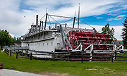"""The Riverboat Nenana is a sternwheeler nicknamed the """"Queen of the Yukon"""", a National Historical Landmark now displayed in Pioneer Park, Fairbanks, Alaska, USA. She was commissioned by the Alaska Railroad and built in 1933. Her parts were made in Seattle and then shipped to Nenana, Alaska where she was constructed. She plied the Tanana and Yukon Rivers from 1933 to 1954, primarily running the 858 miles between Nenana and Marshall. Although mainly a cargo ship, she also slept up to 50 passengers and was complete with showers and flushing toilets. She could hold up to 300 tons of cargo and push six barges on the Tanana. However, on the Yukon she only pushed one barge at a time because of the river's curves and treacherous conditions. The sternwheeler traveled 17 mph downriver and 7 mph upriver. She is the world's second largest existing wooden hull vessel (237 feet long, 42 feet wide, 5 decks high).  Pioneer Park, run by the Fairbanks North Star Borough Department of Parks and Recreation, commemorates early Alaskan history with museums and historic displays. Pioneer Park was opened in 1967 as Alaska 67 Centennial Exposition to celebrate the centennial of the Alaska Purchase. After being given first to the state and then to the city, Mayor Red Boucher renamed the site Alaskaland, which was changed to its present name in 2001."""