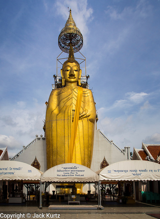 """15 AUGUST 2014 - BANGKOK, THAILAND:   The standing Buddha statue at Wat Intharawihan. Wat Intharawihan (also called Wat Intharavihan) is a Buddhist temple located in the Nakhon District of Bangkok, Thailand. It was built at the beginning of the Ayutthaya period and was originally called Wat Rai Phrik. The best known feature of the temple is a 32 meter high (105 feet), 10 meter wide (33 feet) standing Buddha referred to as Luang Pho To or """"Phra Si Ariyamettrai."""" It took over 60 years to complete and is decorated in glass mosaics and 24-carat gold. The topknot of the Buddha image contains a relic of Lord Buddha brought from Sri Lanka.      PHOTO BY JACK KURTZ"""